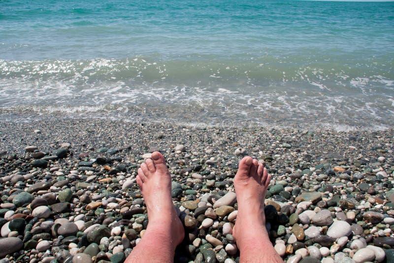 Pés do ` s do homem na praia foto de stock royalty free