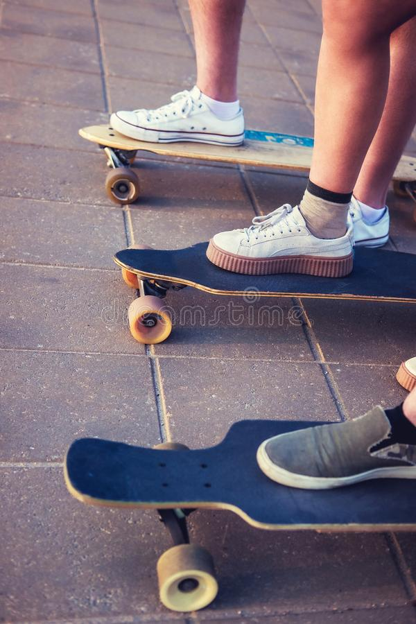 Pés do ` s do skater em longboards fotografia de stock royalty free