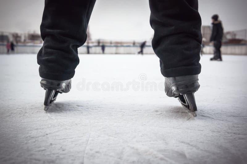 Pés do skater na pista de patinagem Cor preta dos patins de Pés em calças pretas na patinagem no gelo O amador ostenta o passatem foto de stock royalty free