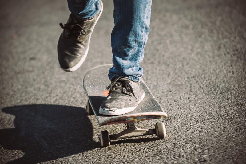 Pés do skater que montam o skate na rua imagem de stock royalty free