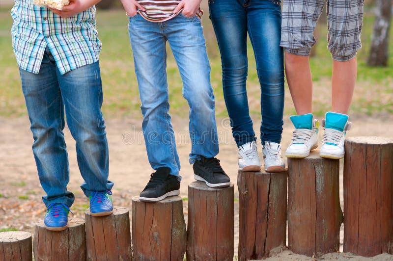 Pés dos adolescentes que estão em colunas de madeira imagem de stock