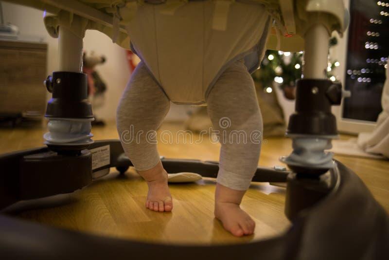 Pés dos bebês em um caminhante do bebê imagens de stock