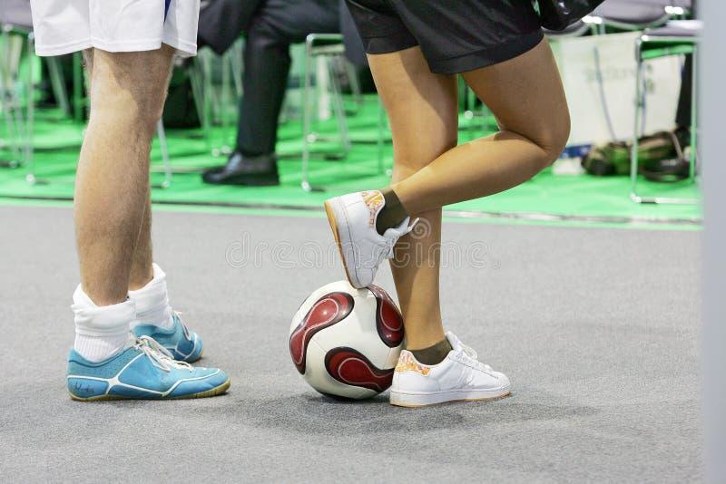 Pés dos desportistas com futebol foto de stock