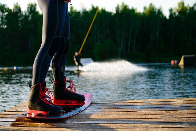 pés dos homens s em um wakeboard imagem de stock