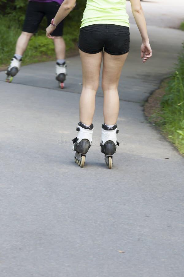 Pés dos patins de rolo da equitação da menina imagens de stock