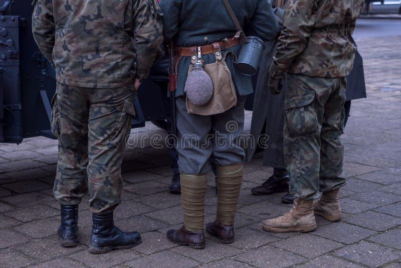 Pés dos soldados das eras diferentes sapatas, uma garrafa para a água, uma faca fotografia de stock