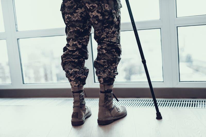 Pés dos soldados do close up que inclinam-se na muleta pela janela fotos de stock royalty free
