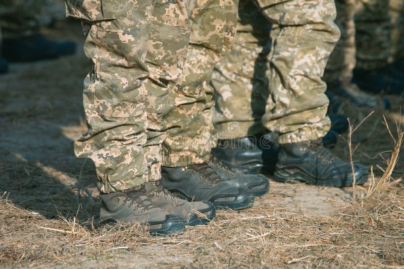 Pés dos soldados no uniforme militar e botas que estão na linha no acampamento imagem de stock