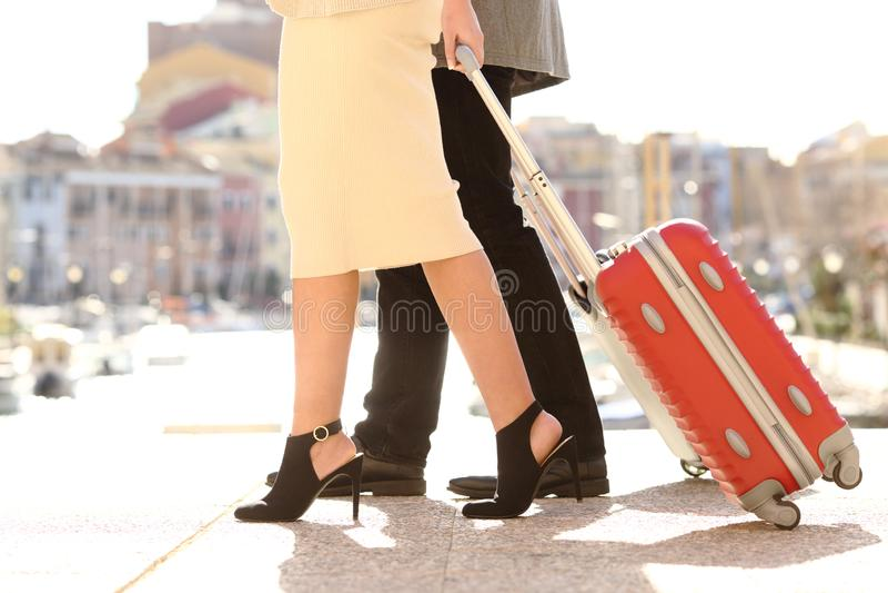 Pés dos turistas que puxam as malas de viagem que andam na rua imagens de stock