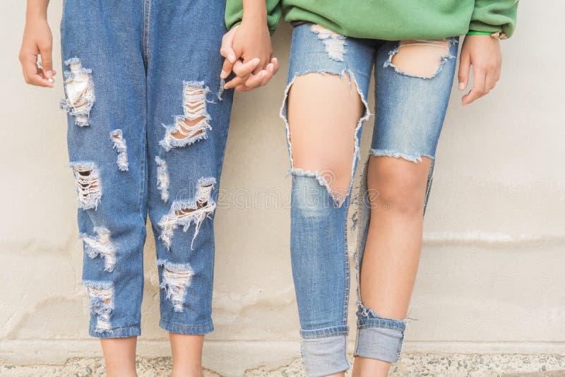 Pés e calças de brim dos adolescentes imagem de stock
