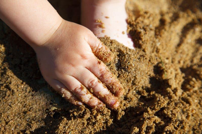Pés e mão do bebê na areia imagem de stock royalty free
