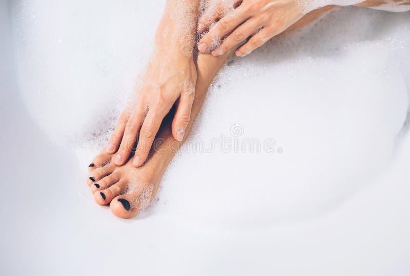 Pés e mãos bons do ` s da mulher da preparação no fim da espuma do banho acima da imagem imagem de stock