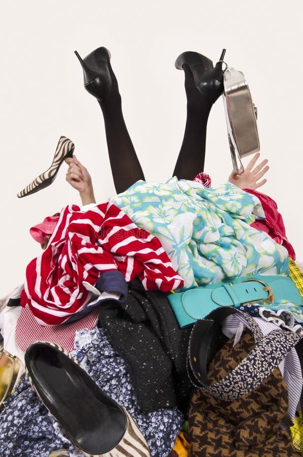 Pés e mãos da mulher que alcançam para fora de uma pilha grande da roupa e dos acessórios fotos de stock royalty free