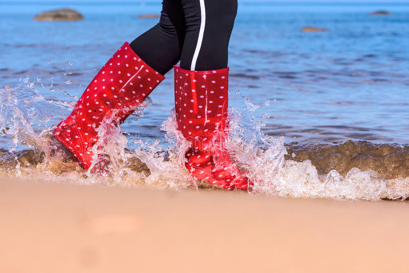 Pés em botas de borracha vermelhas fotos de stock royalty free