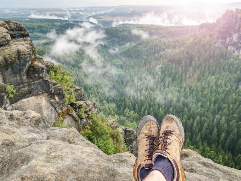 Pés em botas de couro alaranjadas pretas na cimeira da montanha fotos de stock