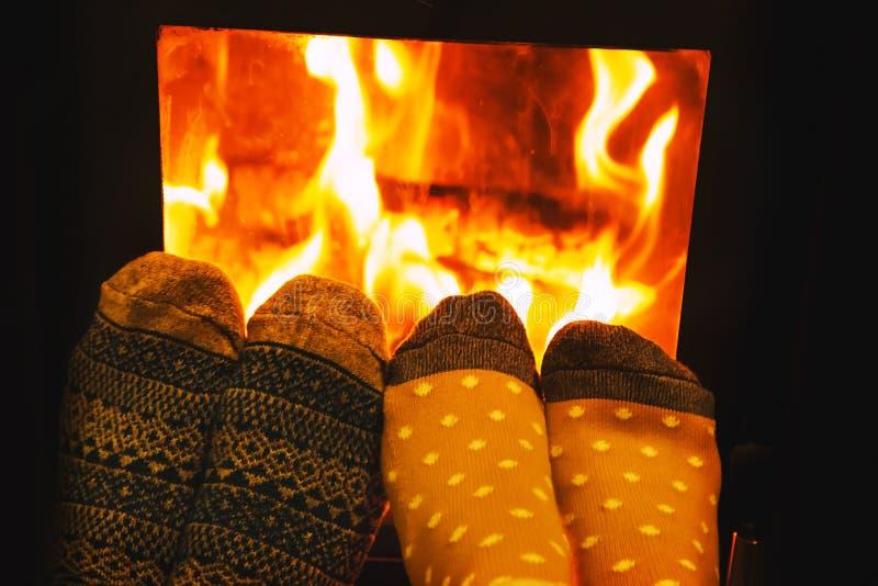 Pés em peúgas de lãs dos amantes dos pares que aquecem-se pelo fogo acolhedor imagens de stock