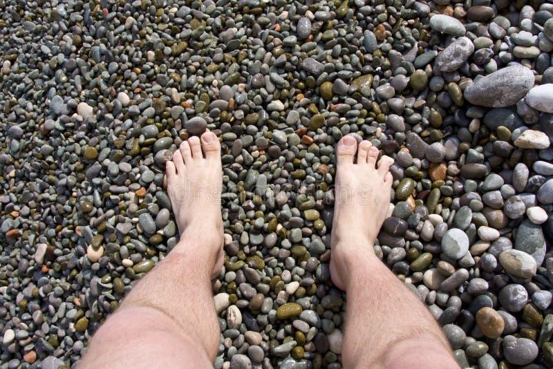 Pés em pedras do mar fotografia de stock royalty free