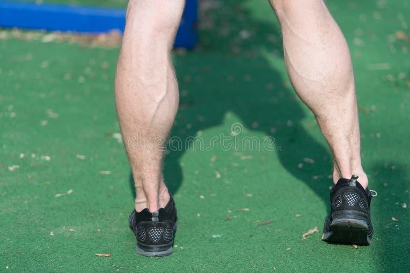 Pés em sapatas pretas da forma do esporte na grama verde Pés musculares com as veias no estádio ou na arena em exterior ensolarad foto de stock