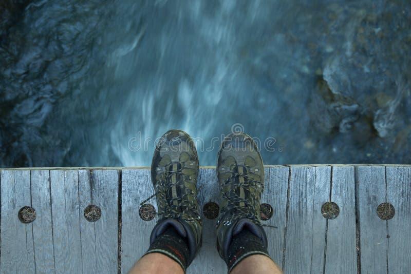 Pés em uma ponte de madeira com água de fluxo - para baixo abaixo foto de stock royalty free