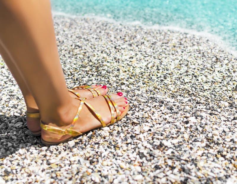 Pés fêmeas bonitos na areia do mar fotografia de stock