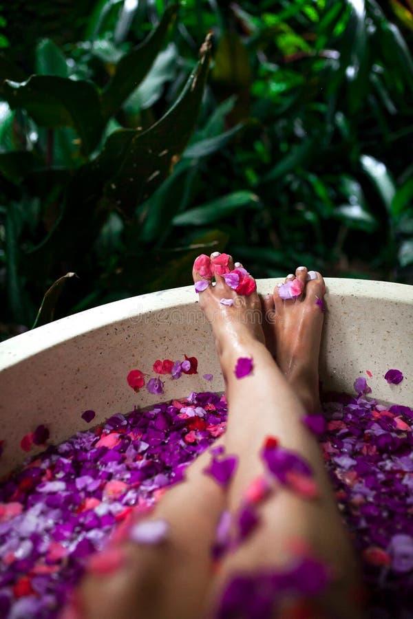Pés fêmeas bonitos no banho exterior com flores tropicais Termas, fotografia de stock