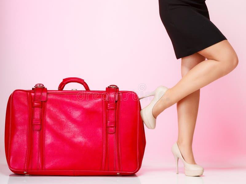pés fêmeas com a mala de viagem vermelha no rosa. Curso. fotos de stock