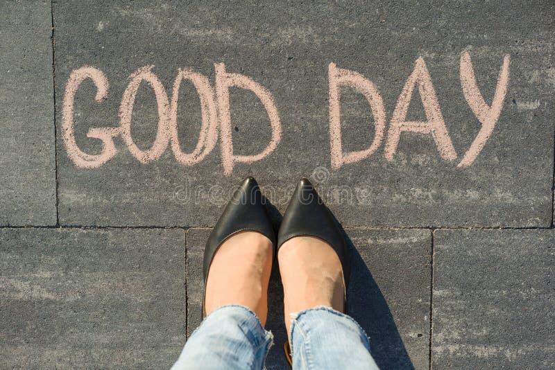 Pés fêmeas com o bom dia do texto escrito no passeio cinzento foto de stock