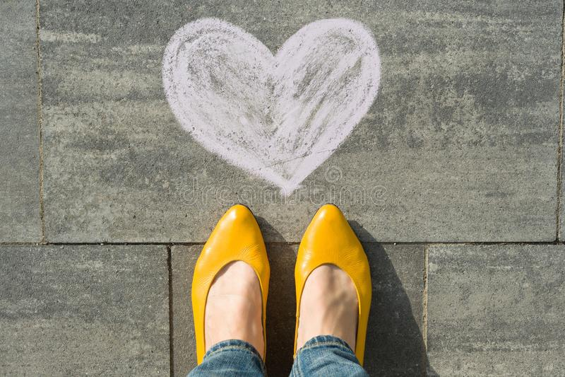 Pés fêmeas com o coração do símbolo pintado no asfalto imagens de stock royalty free