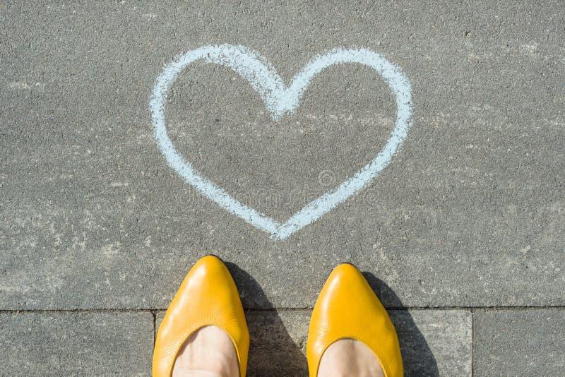 Pés fêmeas com símbolo do coração azul pintado no asfalto imagem de stock
