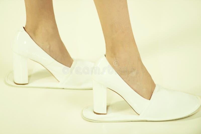 Pés fêmeas da menina nas sapatas e nos deslizadores elegantes de couro imagens de stock