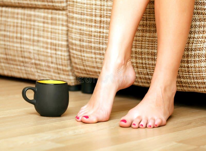 Pés fêmeas e um copo do chá ou do café fotografia de stock royalty free