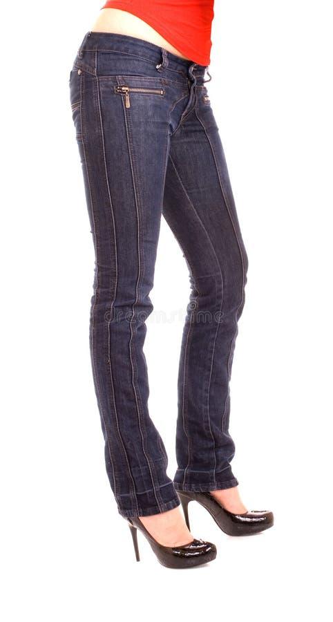 Pés fêmeas elegantes nas calças de brim fotos de stock royalty free