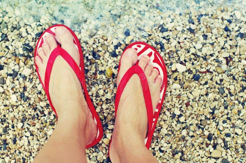 Pés fêmeas em falhanços de aleta vermelhos em uma praia contra o mar em um dia ensolarado do verão fotos de stock royalty free