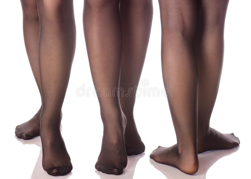 Pés fêmeas em meias pretas das calças justas da beleza diferente dos sentidos fotografia de stock royalty free
