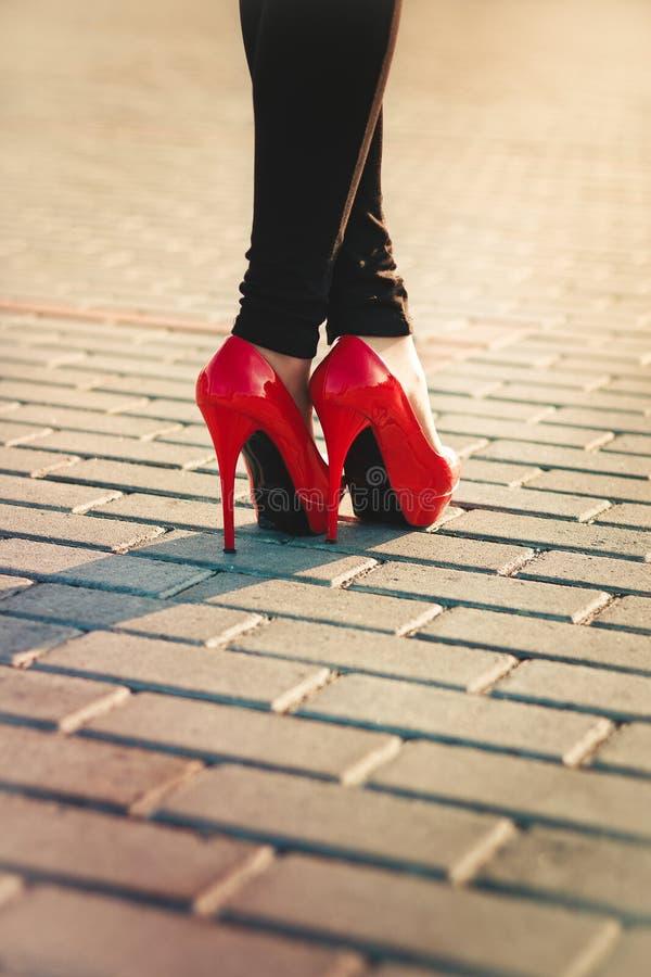 Pés fêmeas em sapatas vermelhas lustrosas com pavimento no b imagens de stock royalty free