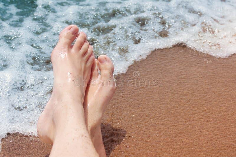 Pés fêmeas em uma praia contra o mar foto de stock