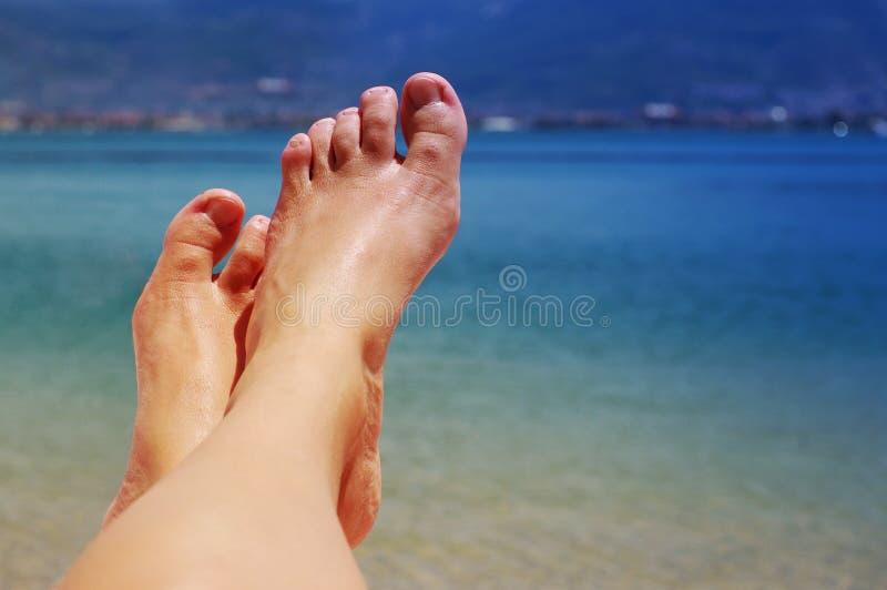 Pés fêmeas em uma praia contra o mar em um dia ensolarado do verão fotografia de stock royalty free