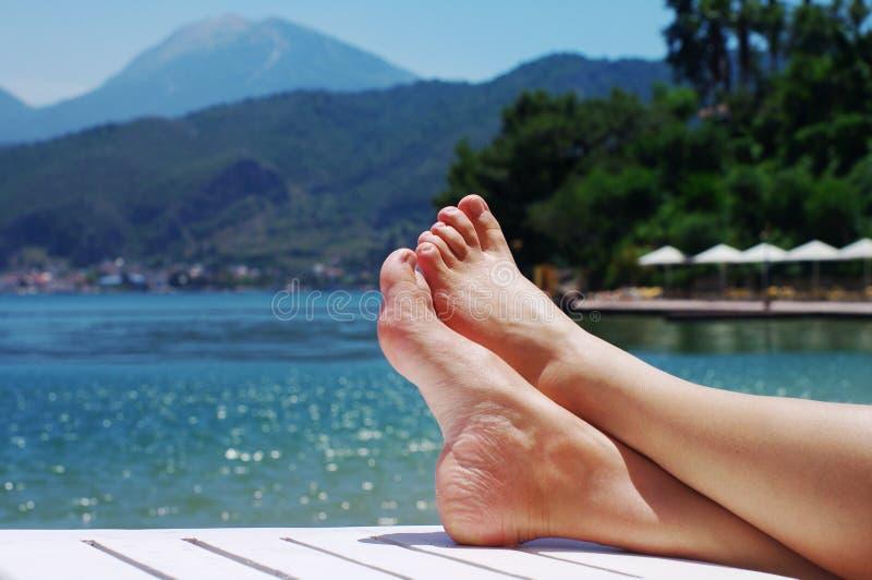 Pés fêmeas em uma praia contra o mar em um dia ensolarado do verão fotos de stock