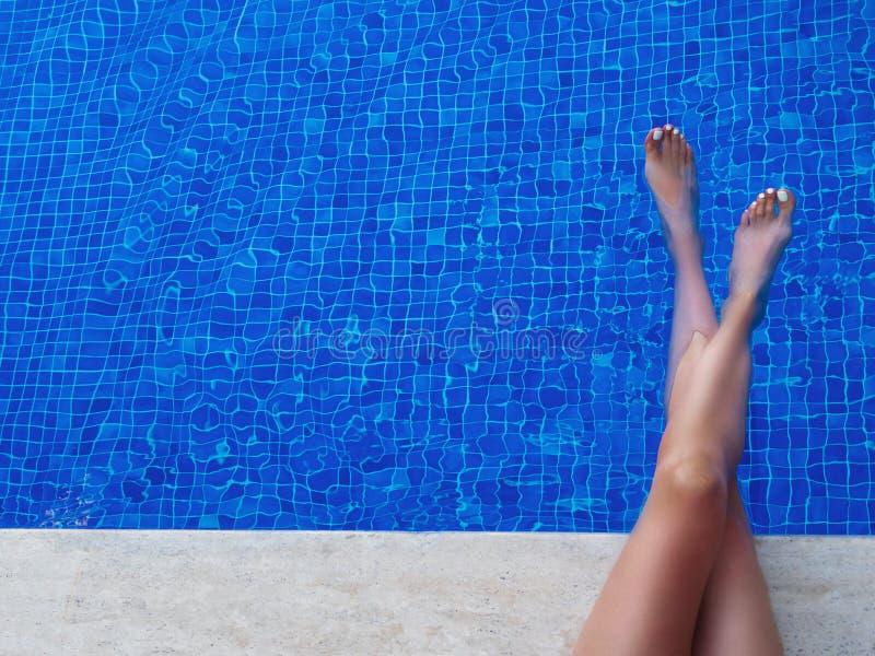 Pés fêmeas em uma toalha branca em um vadio em um fundo da associação de água azul fotografia de stock royalty free