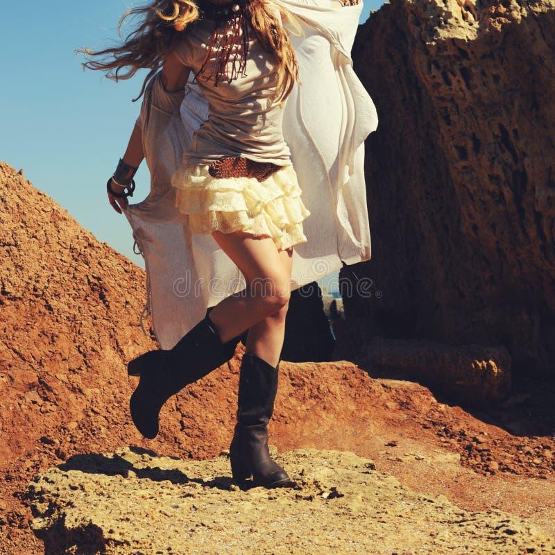 Pés fêmeas magros vestidos nas sapatas de couro do vaqueiro com a saia curto do laço, mulher da forma foto de stock