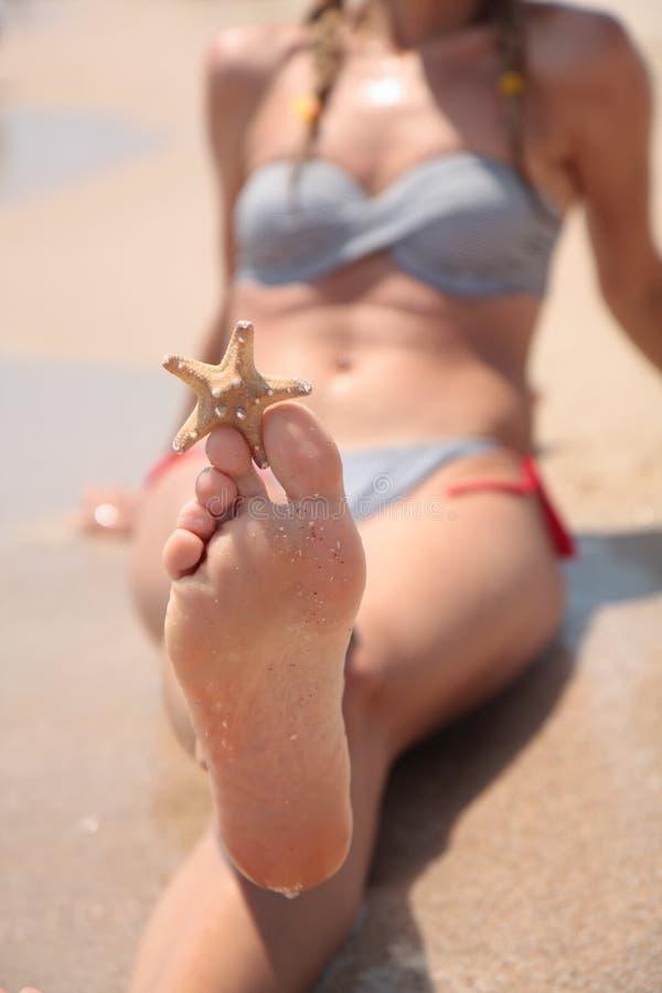 Pés fêmeas molhados na praia e na areia fotos de stock royalty free