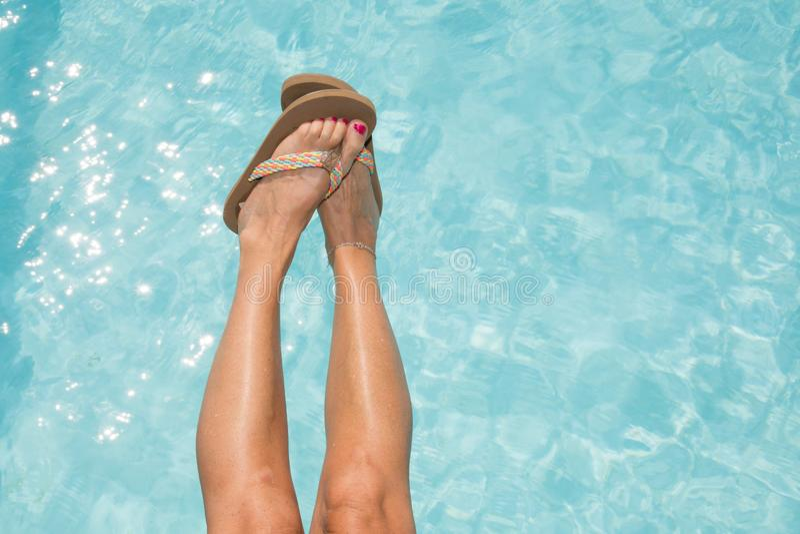 Pés fêmeas na água azul da piscina fotografia de stock royalty free