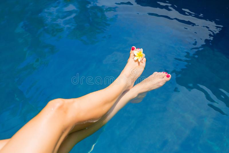 Pés fêmeas na agua potável azul imagem de stock royalty free