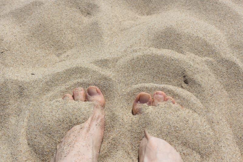 Pés fêmeas na areia fotografia de stock