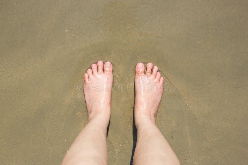 Pés fêmeas na areia foto de stock