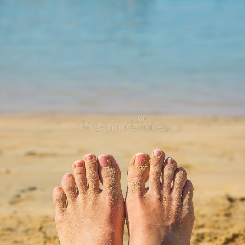 Pés fêmeas na areia contra a praia e o mar foto de stock royalty free