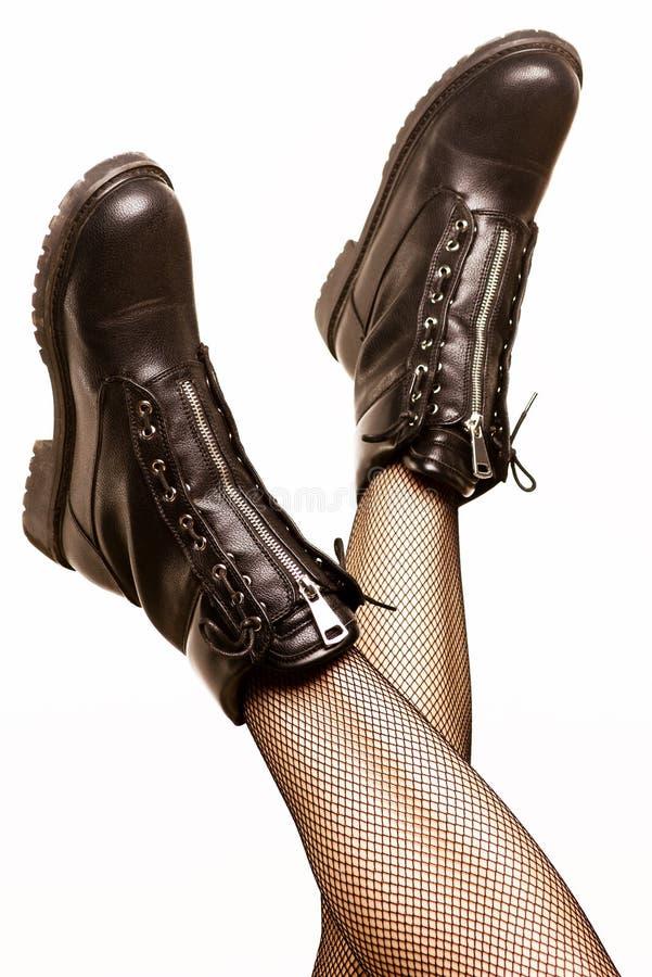 Pés fêmeas na meia-calça 'sexy' e em botas pretas do exército imagens de stock