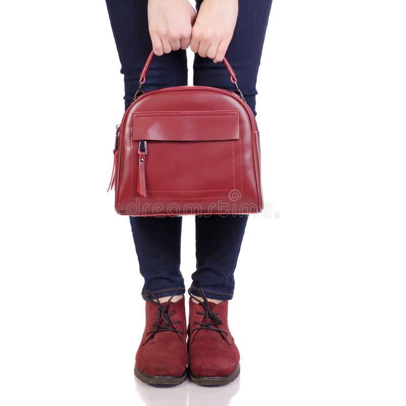 Pés fêmeas nas calças de brim e em sapatas vermelhas da camurça com a bolsa vermelha do saco de couro imagens de stock royalty free