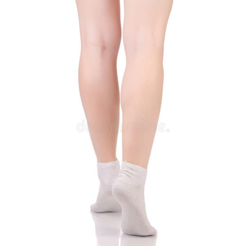 Pés fêmeas nas peúgas bege brancas do algodão fotografia de stock royalty free
