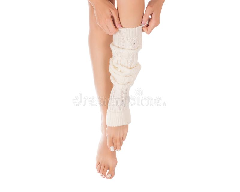 Pés fêmeas no aquecedor do pé branco Mãos fêmeas que põem sobre umas polainas Pedicure branco, tratamento de mãos francês Feche a imagens de stock royalty free